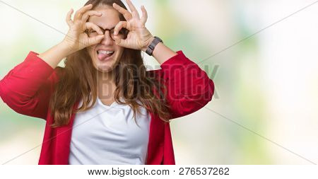 Beautiful plus size young business woman wearing elegant jacket and glasses over isolated background doing ok gesture like binoculars sticking tongue out, eyes looking through fingers. Crazy