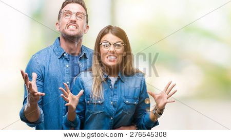 Young couple in love wearing glasses over isolated background crazy and mad shouting and yelling with aggressive expression and arms raised. Frustration concept.