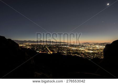 Predawn view of sprawling west San Fernando Valley neighborhoods from rocky peaks in the Santa Susana Mountains above Los Angeles, California.