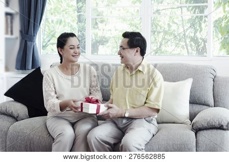Happy Senior Couple Exchanging Gift Box While Relaxing At Home In The Living Room- Image.