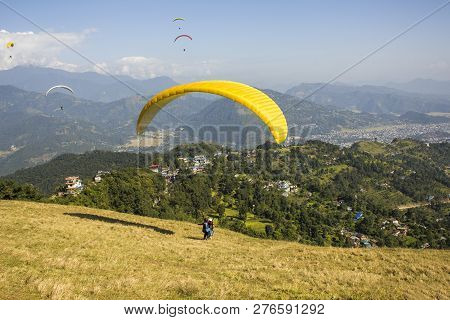 Tandem Paragliders On A Yellow Parachute During Takeoff From The Hillside Against The Background Of