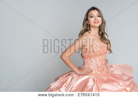 Hispanic teen girl wearing a quinceanera dress for her party