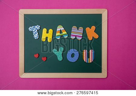 Colorful Letters Shaping The Word Thank You On Green Board With Wooden Frame, Pink Wall Background