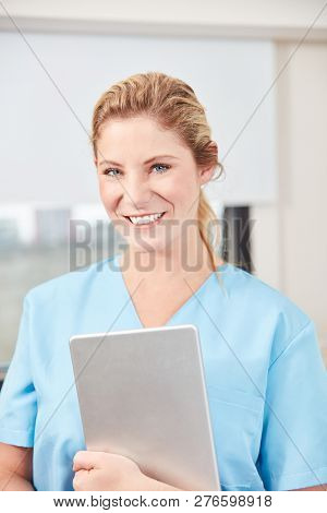 Smiling Woman As Nurse With Tablet Computer In Hospital