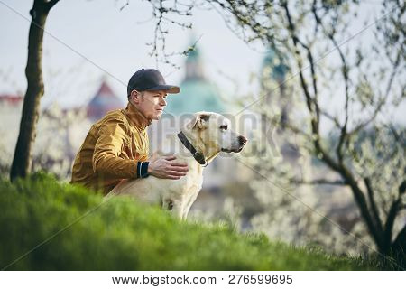 Young Man With His Dog. Pet Owner Relaxation With Labrador Retriever On Grass In Public Park. Prague