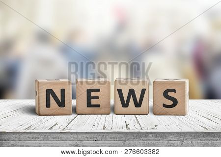 News Sign On A Worn Wooden Table With A Blurry Background In Bright Colors