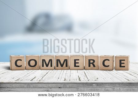 Commerce Word On A Wooden Cube Sign With A Blurry Blue Background On A Desk