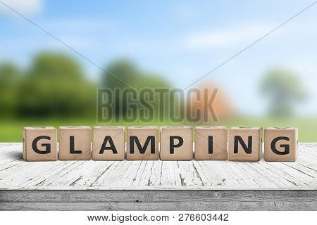 Glamping Sign On Wooden Planks In The Summer With A Green Camping Area In The Background