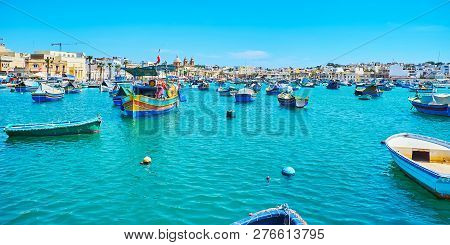 Panorama Of The Port Of Marsaxlokk With Many Wooden Boats And Dinghies, Bobbing On The Waves, Malta.