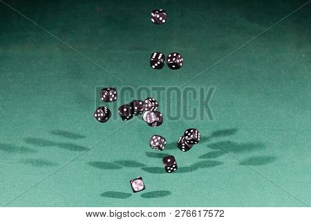Fifteen Black Dices Falling On A Isolated Green Table