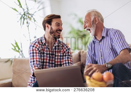 Adult Son Helping Senior Father With Computer At Home
