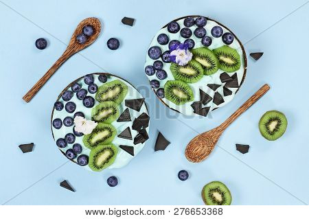 Blue Spirulina And Berry Smoothie Bowl, Fresh Blueberries, Kiwi And Chocolate Pieces With Wooden Spo