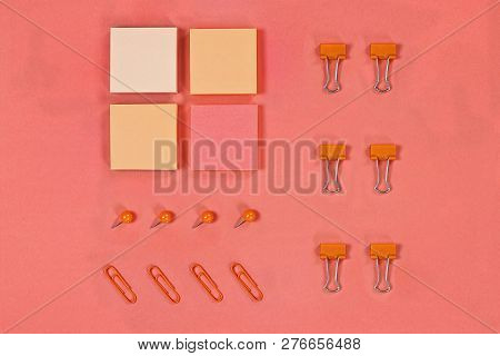 Variety Of Note Pad Paper, Push Pins And Paper Clips For Organizing Over Coral Color Background With