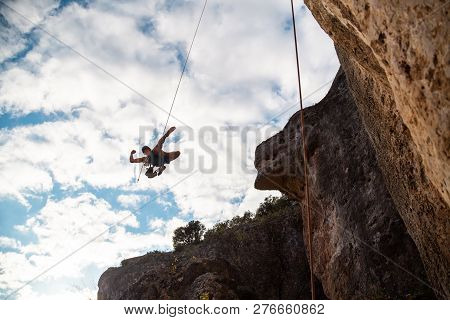 Man In Hardhat Hanging On Rope While Doing Rappel And Showing Pirouettes Flying In Air