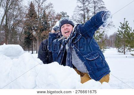 A Senior Man And His Young Son Throwing A Snowball,