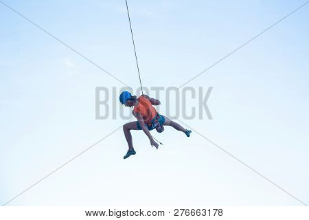 View Of Man In Hardhat Hanging On Rope While Doing Rappel And Showing Pirouettes Flying In Air