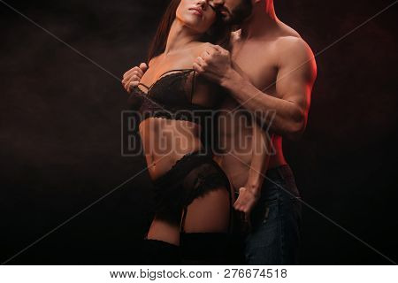 Cropped View Of Passionate Man Undressing Sexy Girlfriend Isolated On Black