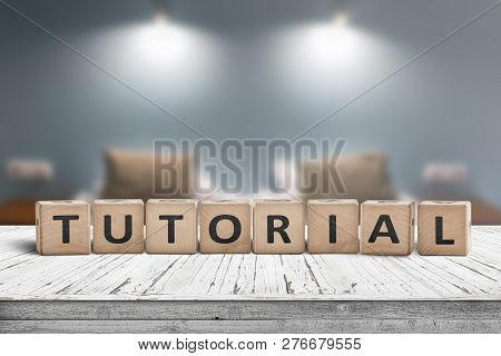 Tutorial Sign On A Wooden Table In A Room With Lights On A Blurry Background