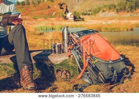 Backpacker On A Trailhead Looking Inside The Map And Enjoying Warm Tea.