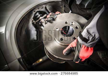 Car Mechanic With Modern Vehicle Brake Disc In Hands. Automotive Theme.