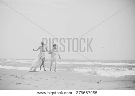 Beautiful Happy Young Wedding Couple Of Man And Woman In White Running Along Ocean Beach Shore On Wi