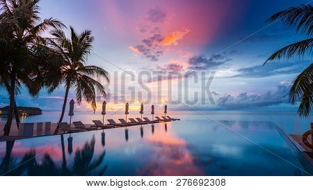 Luxury Infinity Pool Overlooking Sunset Sea And Sky Reflection. Amazing Swimming Pool And Beach Back