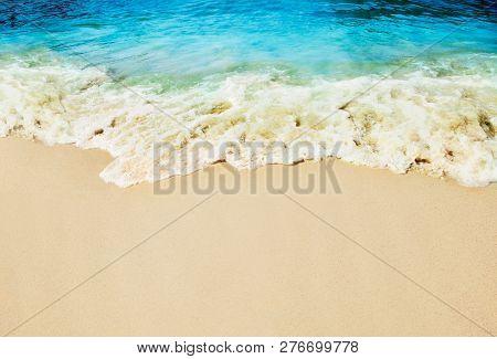 Sandy beach, splashing waves on the seashore.