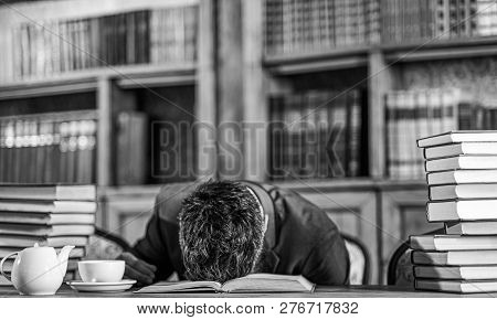 Guy Is Overworked And Sleeps On Table. Man Sits With Head On Table With Many Books. Mature Man Had T