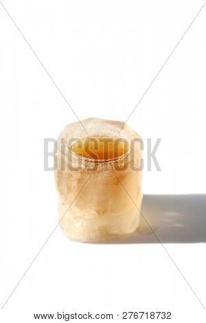 Ice cube Shot Glass. A Shot Glass made from ice. Isolated on white. Room for text. Whiskey Shot Glass made from Frozen Water.