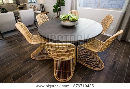 Round Wooden Table With Centerpiece And Wicker Chairs