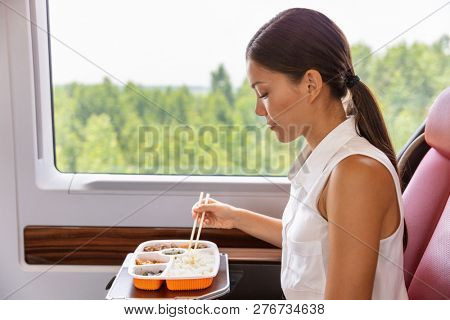 Train commute bus travel Asian business woman eating asian food meal with chopsticks. Businesspeople commuting eating lunch.