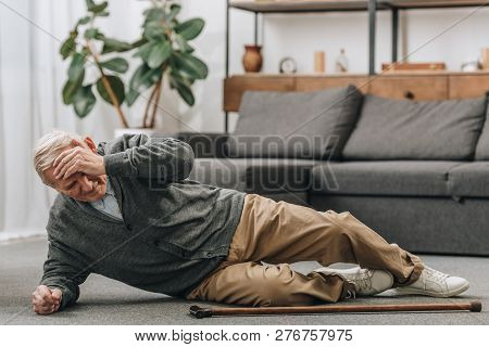 Old Men Falled Down On Floor And Touching Forehead