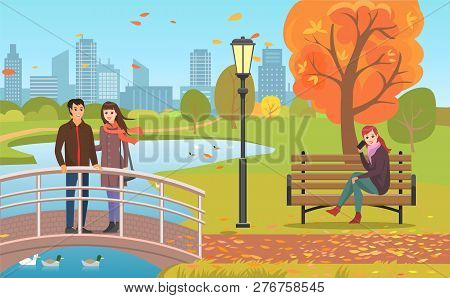 Autumn Park With Pond, Couple Crossing Bridge And Woman On Bench Talking By Phone. Streetlight Among