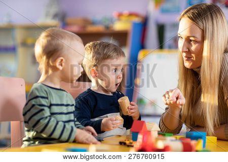Children Building Blocks With Kindergarten Teacher In The Nursery