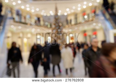 Christmas Sale: Blurred Scene With Dandering Pedestrians In Highly Frequented Shopping Mall