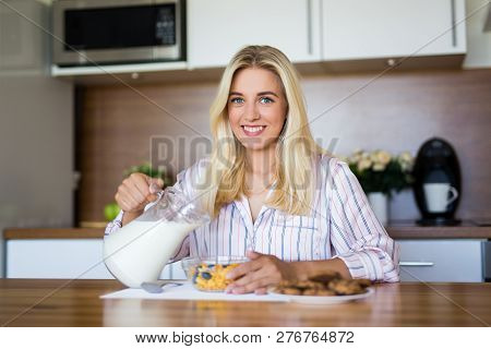 Healthy Breakfast Concept - Woman In Pajamas Pouring Milk In Bowl With Corn Flakes In Modern Kitchen