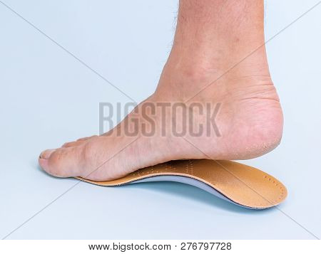 A Man Tries On The Right Leg With Signs Of Flat Feet Orthopedic Insole. Means For The Treatment Of F