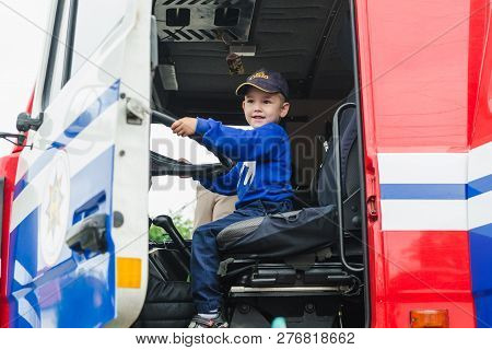 Horki, Belarus - July 25, 2018: The Boy Sits Behind The Steering Wheel In A Red Car Rescue Service 1