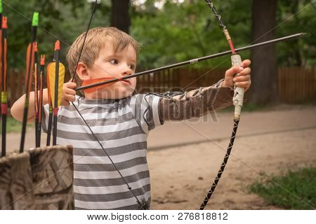 Boy With Bow And Arrow Concentrated On Target. Kid Stared At Target. Child Directed Arrow At A Targe
