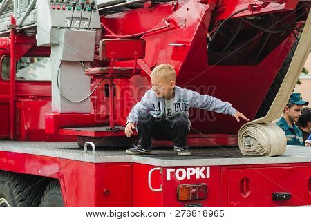 Horki, Belarus - July 25, 2018:the Boy Plays On The Red Cars Of The Rescue Service 112 On A Holiday