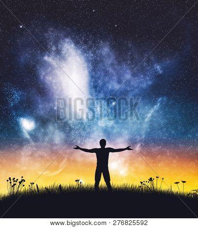 Happy man spreading hands on starry night sky. Freedom, success, winner. Positive energy.