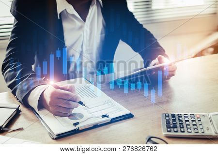 Investor Or Business Man Analysis On Financial Reports And Using Mobile Tablet With Graphic Candle S