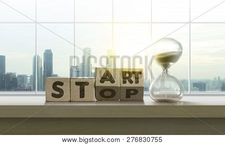 Wooden Blocks With The Word Start-stop And Sand Clock On Table With Panoramic City Skyline Backgroun