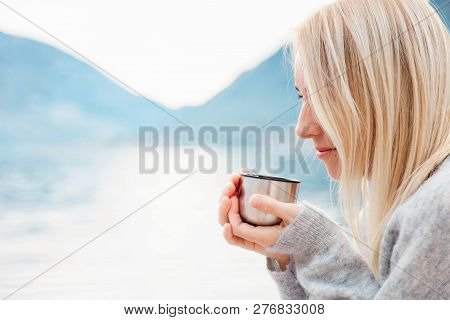 Girl With Mug Of Hot Steamy Beverage By Winter Sea, Mountains. Cozy Picnic With Thermos Of Tea, Coff
