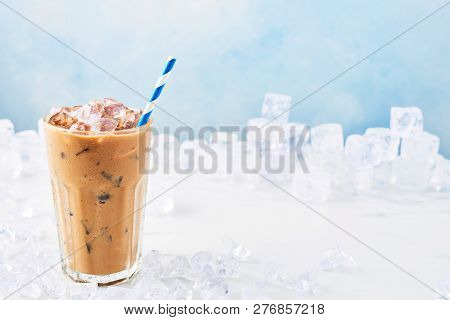 Summer Drink Ice Coffee With Cream In A Tall Glass With Straw Surrounded By Ice On White Marble Tabl