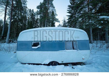 Rundown Camper Trailer In Winter With Trees Behind It.