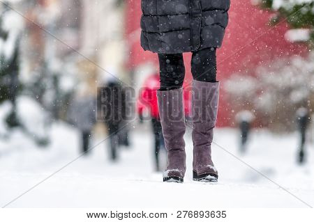Woman Walking On Snowy Sidewalk In Winter City. Close Up Shot On Legs And Shoes