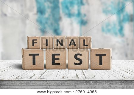 Final Test Spelled With Letter Cubes On A Wooden Table And A Blurry Blue Background