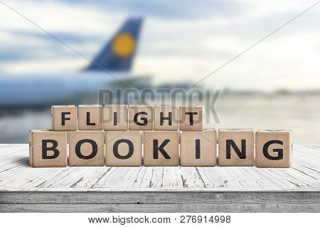 Flight Booking Sign At An Airport With A Plane In The Background
