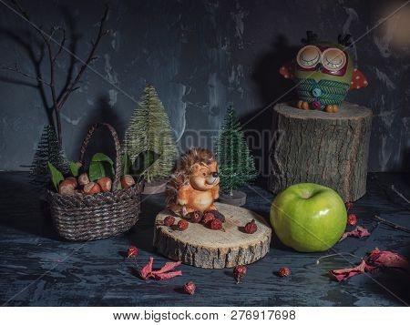 Greeting Card. Toys, Forest Dwellers. The Hedgehog Crouched On A Stump. Near The Basket With The Col